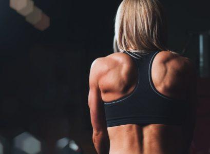 Le dos musclé d'une femme grâce aux tractions